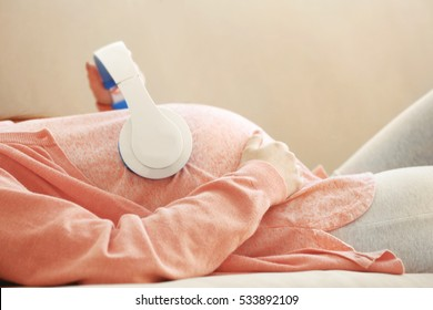 Young pregnant woman with headphones lying on sofa in the room