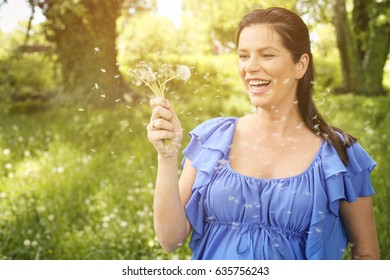 Young pregnant woman holding belly and blowing dandelion.Woman standing on the meadow.