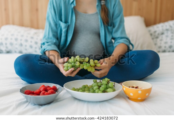 Mulher grávida jovem segurando uvas verdes com um prato de pé ao lado dela. Mulher grávida come comida vegana saudável.