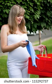 Young pregnant woman holding shopping bags - outdoors