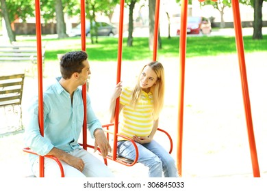 Young pregnant woman with husband on swing outdoors