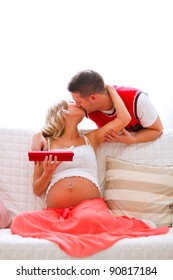 Young pregnant woman kissing her husband who present her jewelery