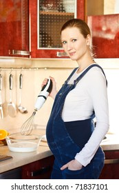 Young pregnant woman in kitchen making a food and smiling