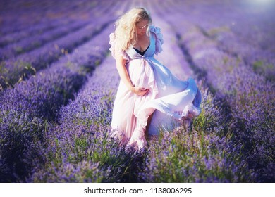 young pregnant woman in light dress walking through the lavender field