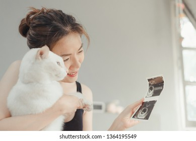 Young pregnant woman looking at 8 Weeks x-ray ultrasound scan of baby