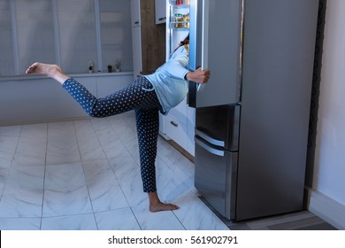 Young Pregnant Woman Looking For Food In Open Refrigerator