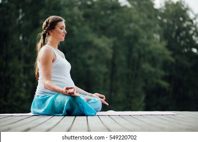 Young pregnant woman in the lotus position is practicing yoga in the forest next to the river. sitting on yoga mats on the wooden pier.