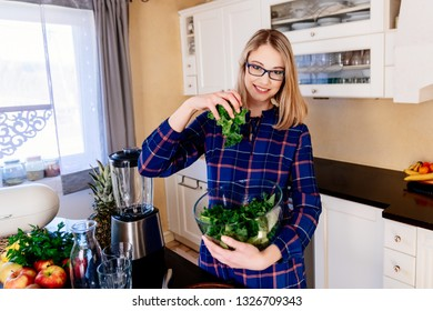 Young pregnant woman mixing green kale in a glass bowl in kitchen. Woman in kitchen. Female preparing delicious healthy fruit and vegetable smoothie