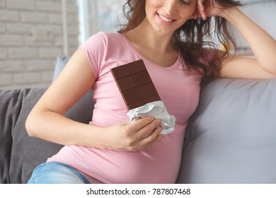 Young pregnant woman on the sofa at home maternity concept eating chocolate close-up
