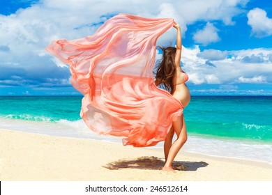 Young pregnant woman with pink cloth fluttering in the wind on a tropical beach. outdoors, healthy pregnancy. Happy pregnant woman on nature. New life concept.