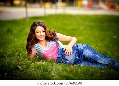Young pregnant woman relaxing in park outdoors, healthy pregnancy.  Beautiful pregnant woman holding her tummy.