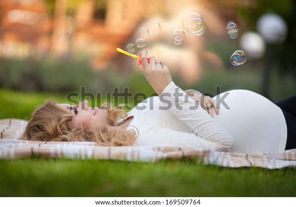 Young pregnant woman relaxing in park outdoors, healthy pregnancy. Happy pregnant woman with bubbles on nature. Beautiful pregnant woman holding her tummy.