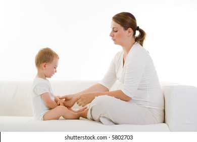 Young pregnant woman sits facing a small child.  Woman is reaching for the child's hand.  Woman is also pregnant.  Both models are in white colored clothing on a white sofa.