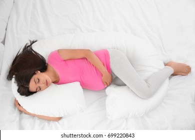 Young pregnant woman sleeping on maternity pillow in bed
