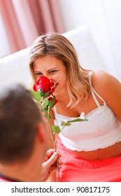 Young pregnant woman smelling flower presented by her husband