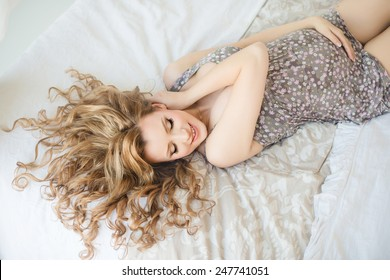 young pregnant woman smiling lying on the bed and touching belly