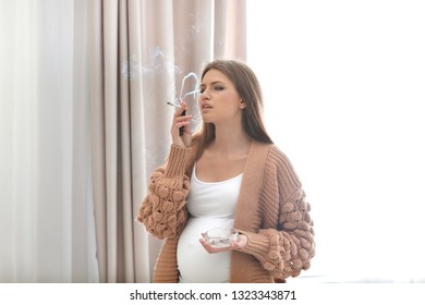 Young pregnant woman smoking cigarette at home. Harm to unborn baby