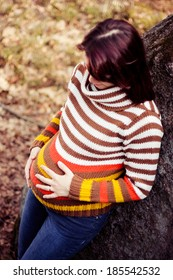 Young pregnant woman in striped pullover stroking her belly, Pregnancy in Autumn, Fall Pregnancy