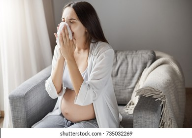 Young pregnant woman suffering from flu. Coughing and using a tissue. Keeping healthy pregnancy is hard.