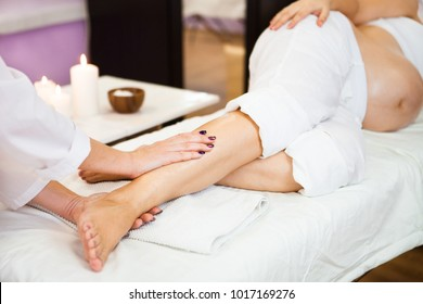 Young pregnant woman take relaxing foot massage at beauty spa salon. Close-up.  Spa treatment. Ð¡oncept of beauty and health