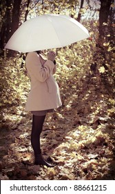 Young pregnant woman under umbrella in autumn forest
