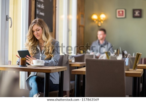Young pregnant woman using digital tablet at table with man sitting in background