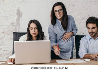 Young pregnant woman at work with her associates in the office while she tells them what to do