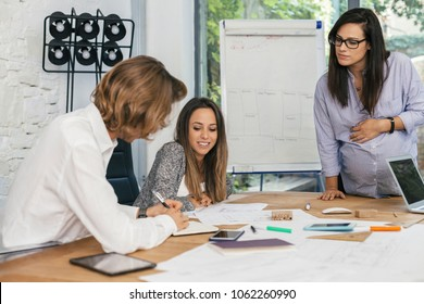 Young pregnant woman at work with his associates in the office during a conference