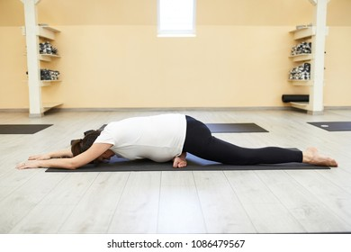 Young Pregnant Women Doing Yoga In The Yoga Studio