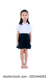 Young preschool child in uniform smiling, a look of enjoyment on face. Full body of cute asian girl standing and looking at camera at studio, isolated on white background. Education and people concept