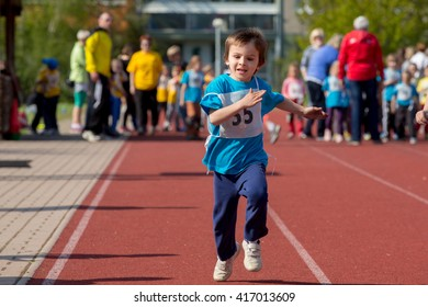 Young preschool children, running on track in a marathon competition, blurred motion