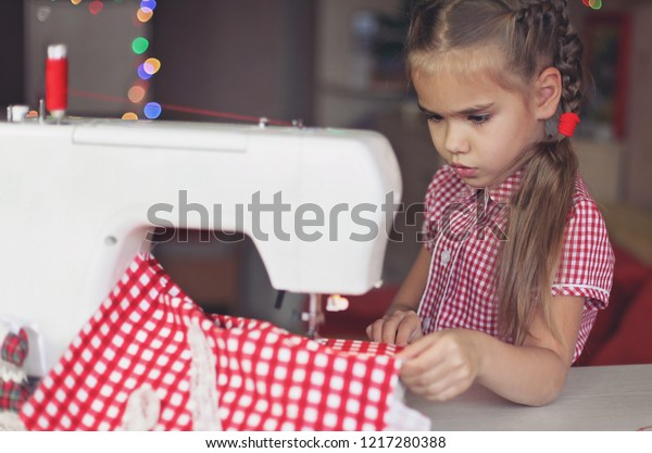 Young preschool girl working on sewing machine, creative tailor workshop, holiday handmade decoration