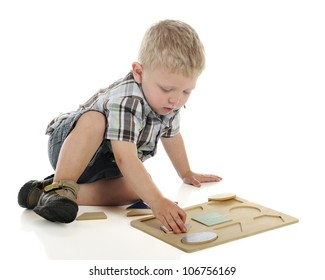 A young preschooler on the floor working on a wooden shape puzzle.  On a white background.
