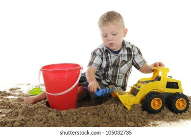 A young preschooler playing in the sand with toy scoops, a pail and a bulldozer.  On a white background.