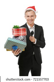 Young presenter in Santa hat with microphone and gift boxes on white background