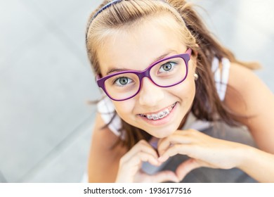 Young preteen girl in glasses wearing braces smiles at the camera showing heart shape with her hands.