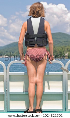 A young preteen girl standing on the front of a pontoon boat with lifejacket on.