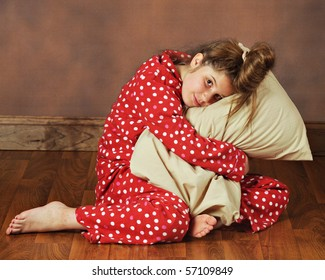 A young preteen in polka-dot pajamas hugging her pillow.