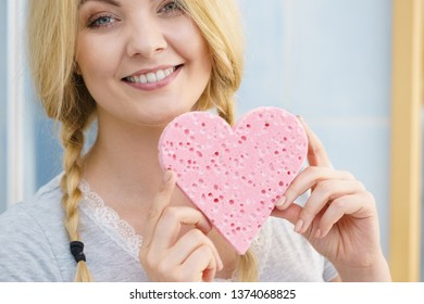 Young pretty adorable woman having two cute braids on blonde hair holding pink sponge in heart shape. Haircare and hairstyling concept.