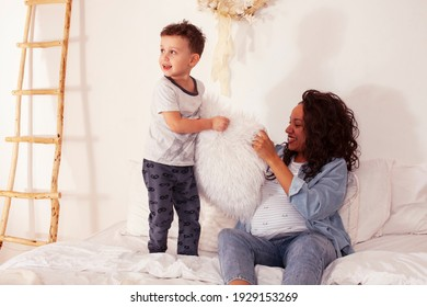 young pretty african americam mother with son in bed at morning playing, happy family, lifestyle people concept