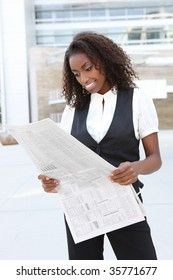 A young pretty african american business woman at office reading newspaper