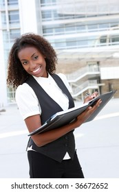 A young pretty african american business woman at office with binder