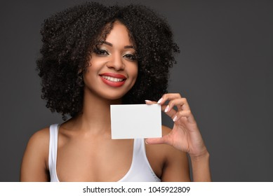 Young pretty African American millennial woman with natural curly hair wearing fashionable white tank top smiling holding a blank poster on a dark gray isolated background.