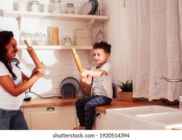 young pretty african american mother with little cute son on kitchen in morning preparing breakfast, lifestyle people concept