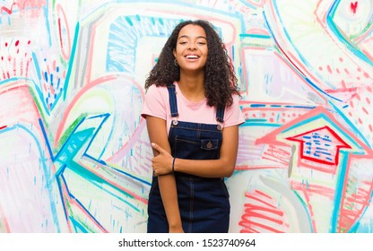 young pretty african american woman laughing shyly and cheerfully, with a friendly and positive but insecure attitude against graffiti wall