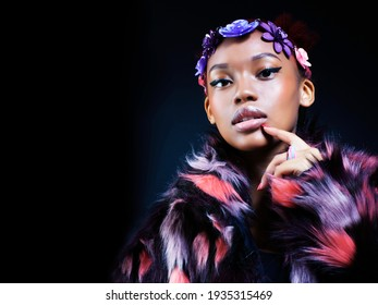 young pretty african american woman in spotted fur coat and flowers on head smiling on black background, fashion people concept