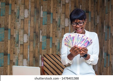 young pretty african girl feeling excited while holding some money in her hand