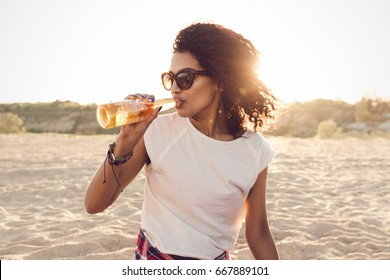 Young pretty african girl in sunglasses drinking beer while having a party at the beach