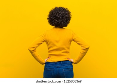young pretty afro woman feeling confused or full or doubts and questions, wondering, with hands on hips, rear view