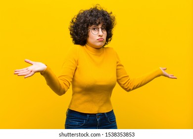 young pretty afro woman feeling puzzled and confused, unsure about the correct answer or decision, trying to make a choice